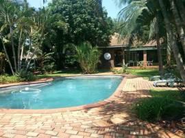 zwembad met ligstoelen en deel achterkant van het huis