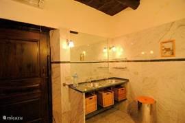 De badkamer heeft twee wastafels van roestvrij staal en een groen marmeren blad.
