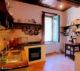De keuken heeft een authentiek karakter. Er is een koelkast met vriesvak, oven, magnetron, vierpits gasstel,een granieten aanrechtblad en volop keukenkgerij.