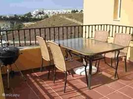 Het balkon met tuinset en ligstoelen