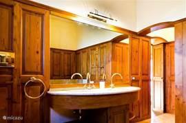 De badkamer op de begane grond Uitgevoerd in marmer en notenhout. Met bad, grote douche, toilet en bidet. Dubbele wastafel.