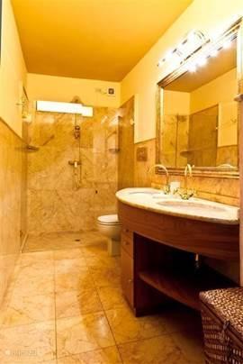 Een de marmeren badkamers met douche, dubbele wastafels etc