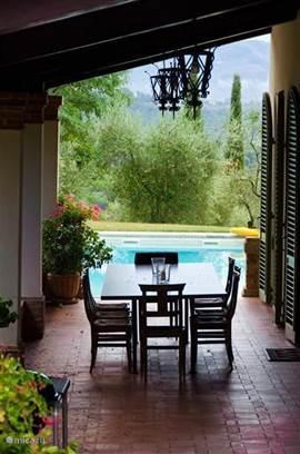 Dineren   all aperto  in de grote Loggia met uitzicht over de s'avonds verlichte rozentuin en het travertin zwembad