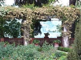 Pergola-terras in rozentuin van Casa delle Rose met doorkijkje op het Toscaanse landschap.