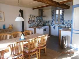 woonkeuken met grote eettafel en zeer ruim assortiment keukenapparatuur en kookbendigdheden
