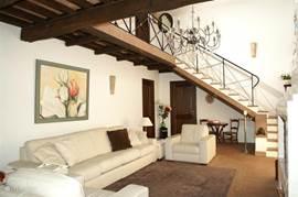 huiskamer met zicht op de La Capriata ( typisch Italiaans dak zoals u ook vindt in de vele cathedralen) en toegang tot de 2e slaapkamer, TV hoek met 5e bed en terras met uitzicht op de Monte Amiata