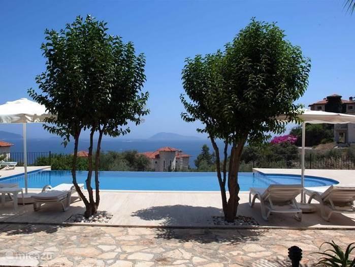 Zwembad met ruim terras en frontaal zeezicht. U ziet hiervandaan het Griekse eilandje Kastellorizo. Vanuit de vissershaven vertrekt regelmatig de ferryboot.