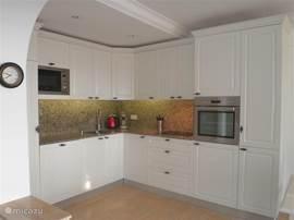 Nieuwe (2013) inbouwkeuken met geintegreerde ruime koelkast, seperaat diepvries, vaatwasser, magnetron, oven en inductie kookplaat. De keuken is voorzien van ruime sortering servies en allerlei keukenbenodigdheden.
