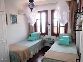 Tweede slaapkamer met twee eenpersoonsbedden, airconditioning en uitzicht op de Middellandse Zee