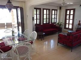 Woonkamer met eethoek, openhaard, airconditioning èn plafondventilator en openslaande terrasdeuren naar de tuin