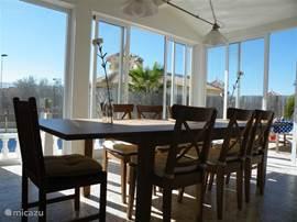 overdekt veranda/serre! Met een heerlijke grote leeftafel en uitzicht over het privezwembad. Voorzien van schuifpuien.
