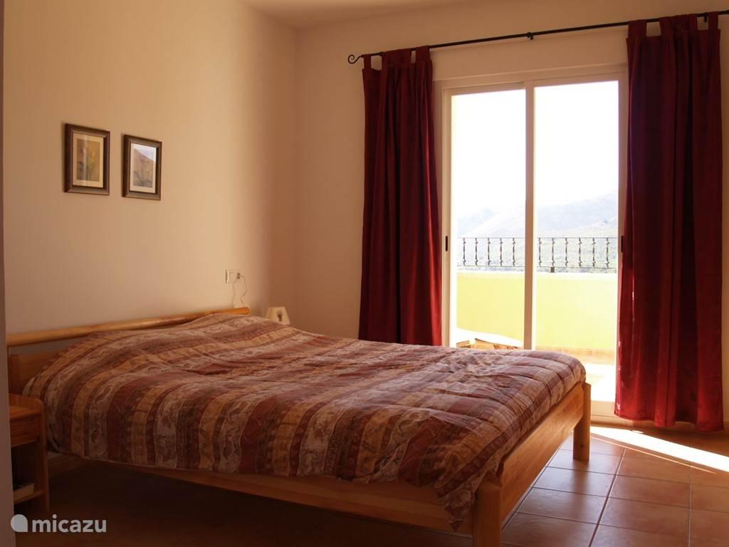 Ouderslaapkamer met tweepersoonsbed en toegang naar zonneterras