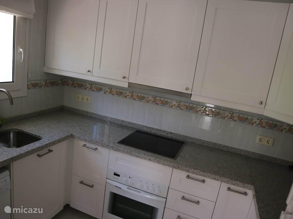 Keuken met links de vaatwasser, in het midden de oven met daar bovenop de kookplaat