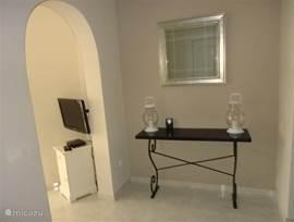 Hal met links de ingang naar de woonkamer en rechts de ingang naar de slaapkamers en badkamers