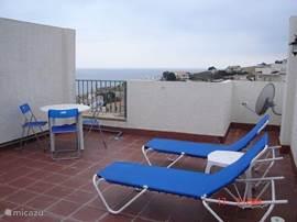 Afgesloten privé dakterras, waar de wasmachine staat. Ligbedden/ parasol en zithoekje. Schitterend uitzicht over de omgeving.