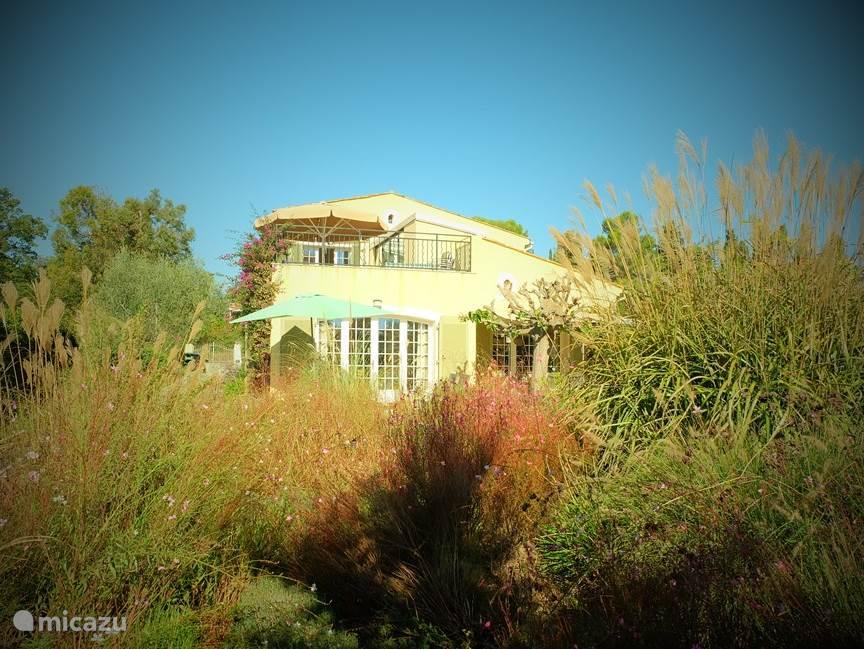 Blik op het huis. Dit huis is met luxe materialen afgewerkt. Boven ziet u het grote terras met daarachter het appartement. Het appartement heeft een eigen opgang, een zeer ruim terras alsmede een eigen tuin met groot schaduwterras. Eigen parkeervoorzieningen en een mooi aangelegde tuin (2011). Tev