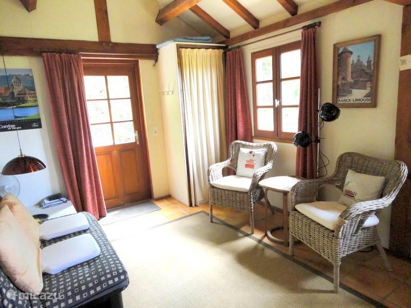 Twee comfortabele fauteuils, slaapbank, hanglegkast, deur naar terras;  links naast de slaapbank is de toegang naar een uitbouw met 2-persoonsbed 1.60x2.00.