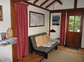 interieur met slaapbank; achter gordijn links: uitbouw met inbouwbed 1.60x2.00; 2 hang/legkasten; keukentje met 2 elektrische kookplaten, oventje, koffiezetapparaat, cd-speler. Er is een goede wifi-verbinding.