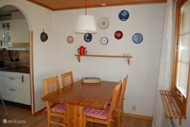 De eethoek, aangrenzend aan de keuken, kijkt uit op de kleine overkapping en veranda.