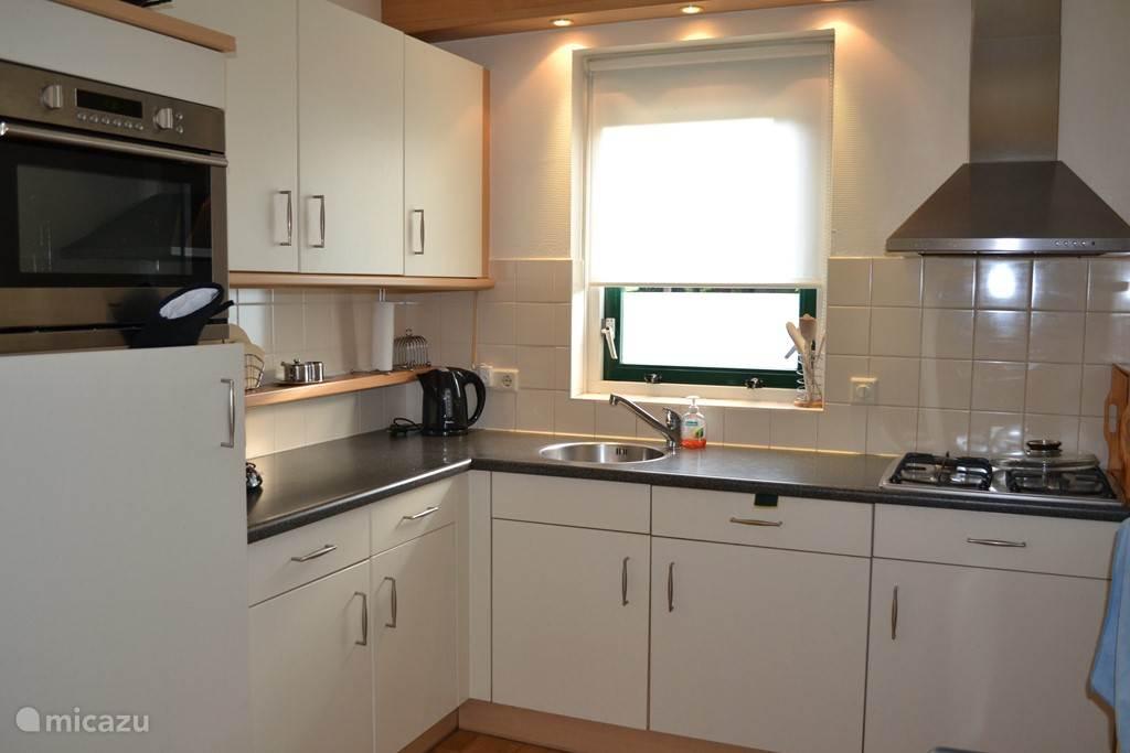 Modern ingerichte keuken voorzien van koelkast met vriesvak, vaatwasser, combi-magnetron en 4 pits gasfornuis.