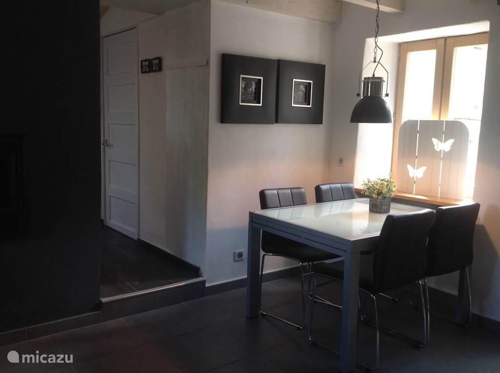 Andere zijde van de living, eethoek-met comfortabele stoelen, doorgang naar de keuken en zicht op voorterras.