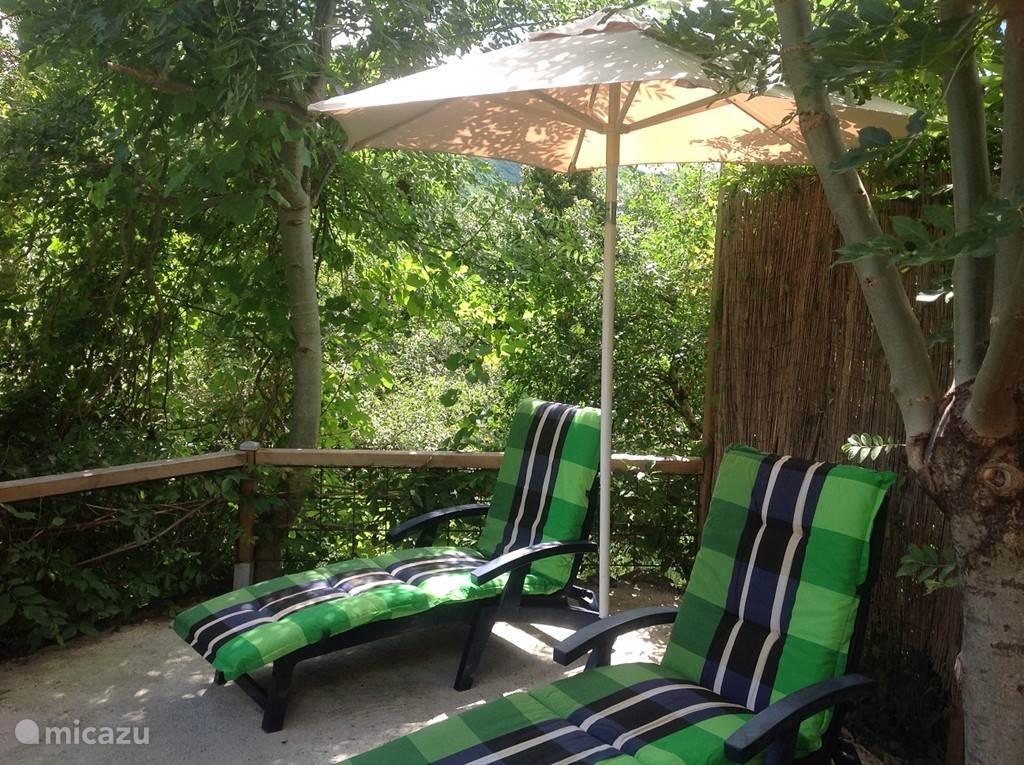 Extra  zonneterras in de beneden tuin(15m2) met ligbedden, kussens en parasol.-omzoomd door bomen, met veel zon  .