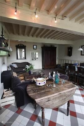 De woonkamer met openhaard en houtkachel. Het huis is voorzien van diverse spelletjes, tv-dvd, woonbladen, romans etc.