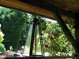 De veranda achter de slaapkamer, waar je heerlijk kunt zitten en genieten van de mooie tuin en de vogelgeluiden.