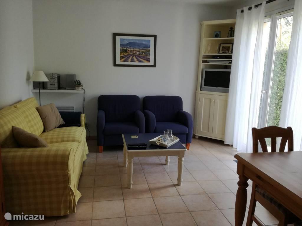 De gezellige woonkamer met openslaande deuren naar het terras.