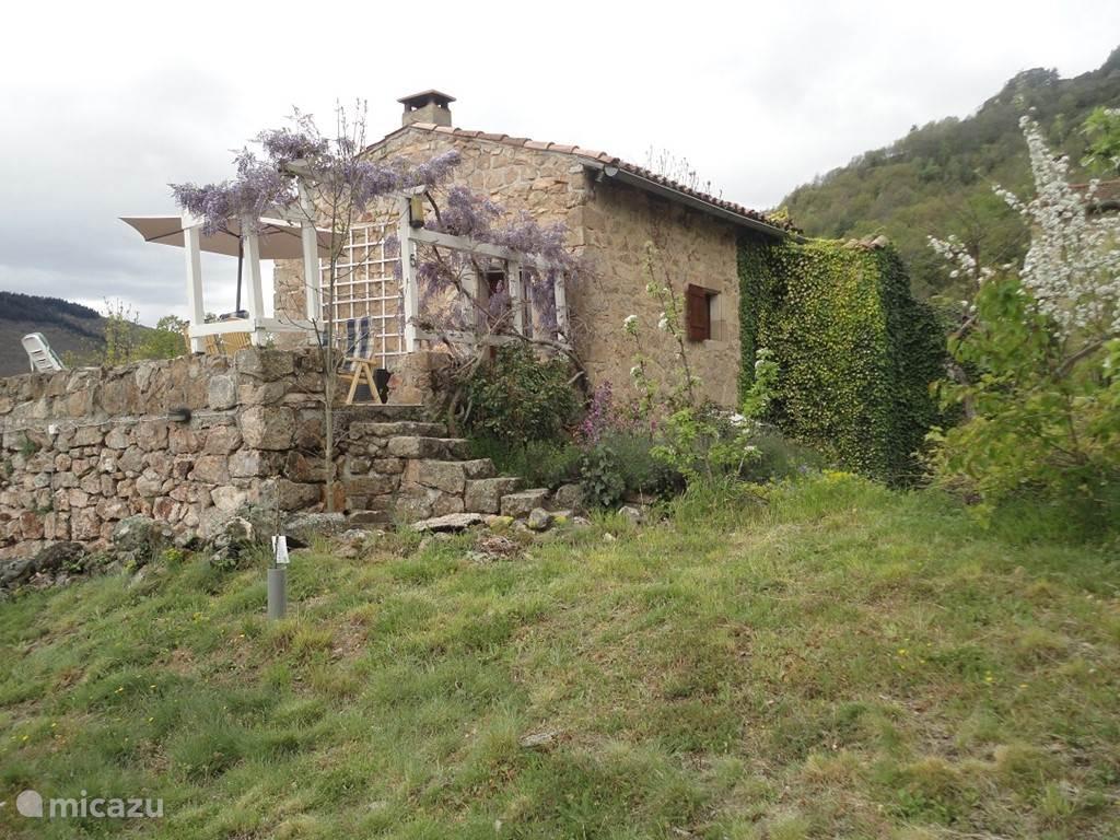 L'Amande is een vrijstaand huis, vooraanzicht, stenentrap naar betegeld boventerras(25m2) met magnifiek uitzicht op de bergen, veel zon(zuiden) Hartman diningset en zonneligbed.+parasol.