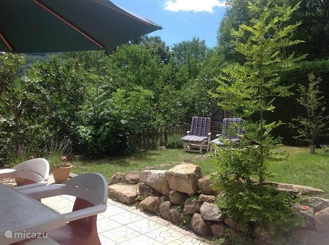 Benedentuin, aangrensend aan de woon-eetkeuken met veel privacy, deels betegeld(25m2), deels gazon( 25m2) en omzoomd door hederahaag, vijgenbomen en coniferen. Af te sluiten middels tuinpoort.