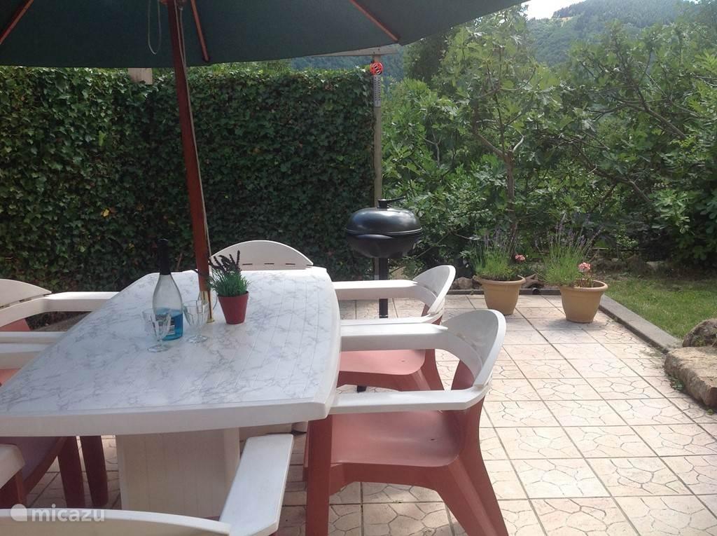 Omsloten terras(25m2 betegeld, met tuinset en parasol, 25m2 gazon, met afsluitbare poort, omzoomd door groen, hedera haag, vijgenbomen en coniferen. Voorzien van electrische kogel bbq.