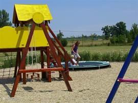 De speeltuin met klautertoestellen en trampoline.