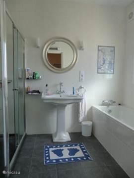 badkamer ensuite bij de hoofdslaapkamer met toilet, bad en ruime douche