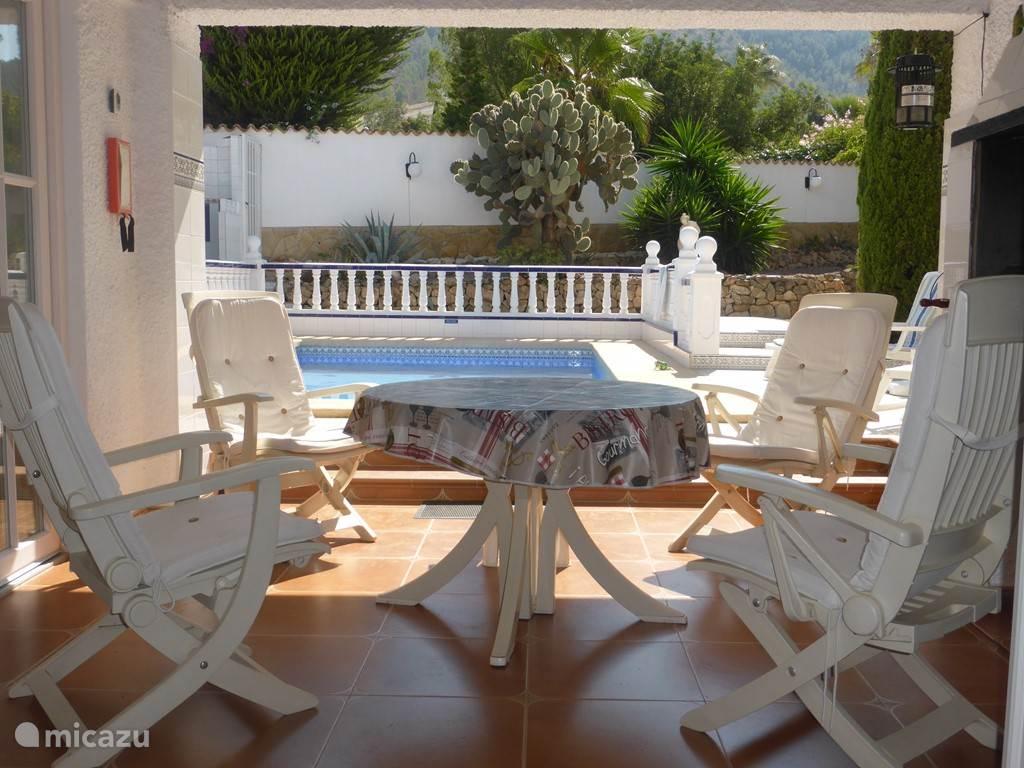zicht vanuit de woonkamer op terras en zwembad