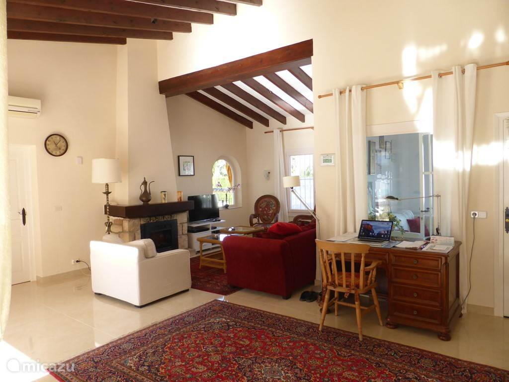 huiskamer met aangrenzende eetkamer en openslaande deuren naar het terras