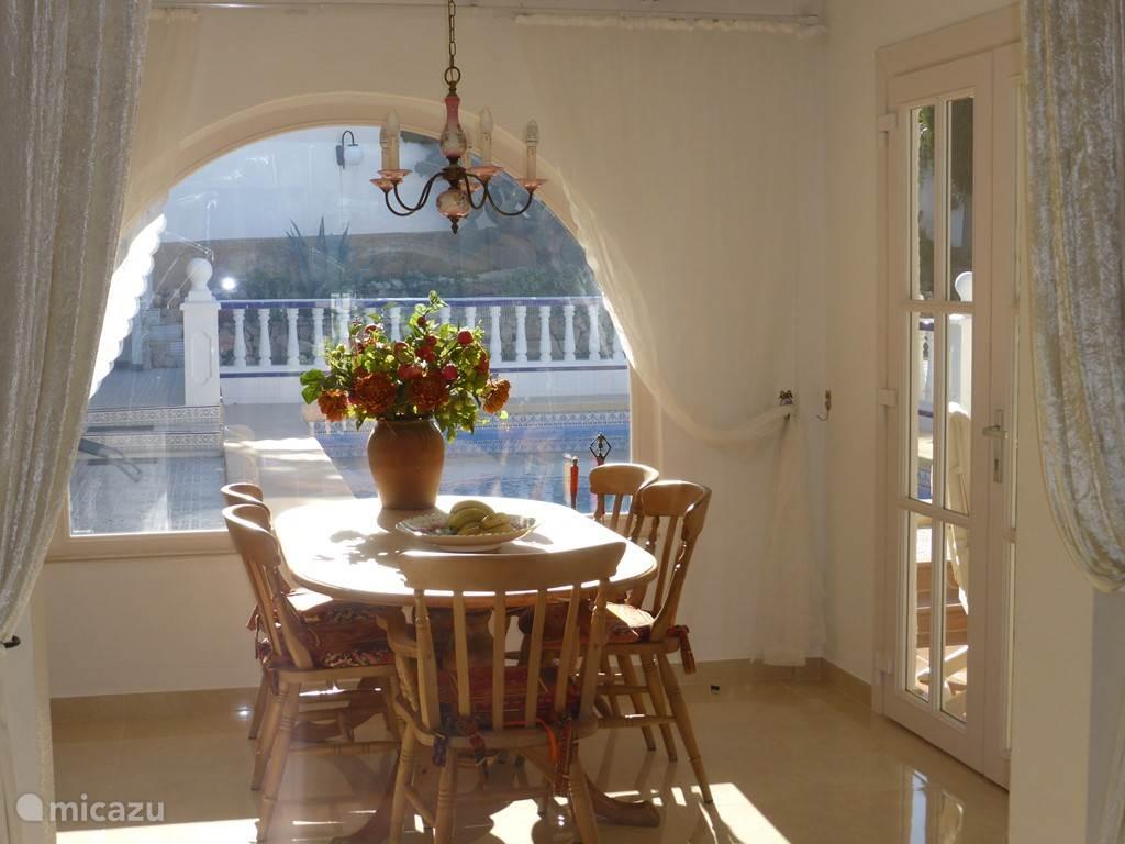 De eetkamer met het uitzicht op de bergen en de achtertuin met zwembad