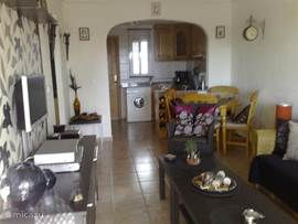 Inrichting huiskamer met open keuken,vanuit de keuken loopt u door naar het achter terras.