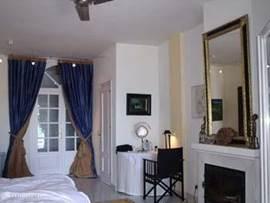 Slaapkamer beneden, rechts de open haard en TV