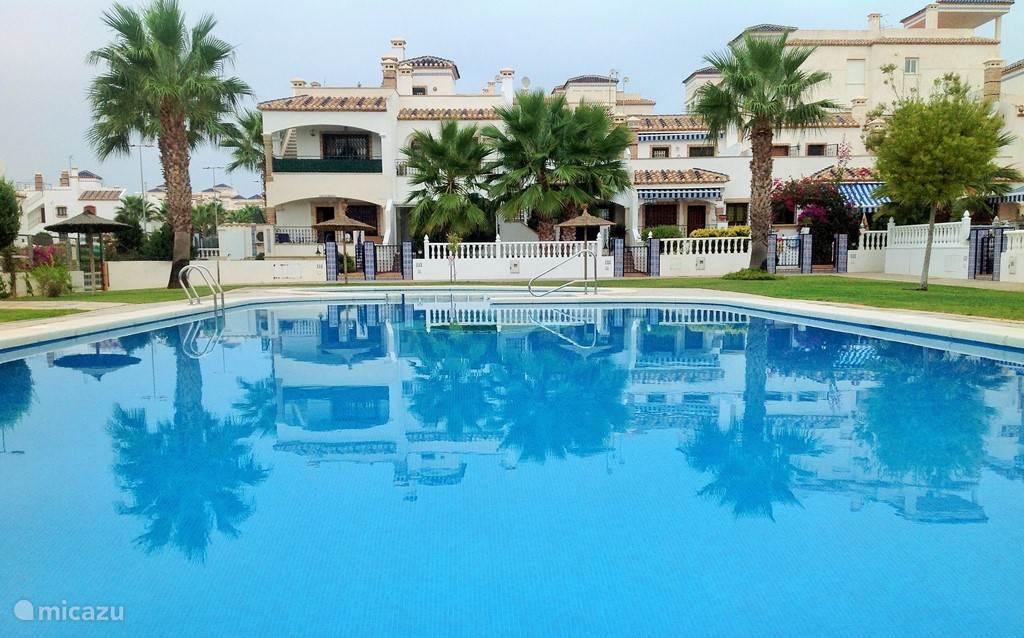 het grote zwembad vanaf de overkant waarbij de woning aan de linkerkant staat.