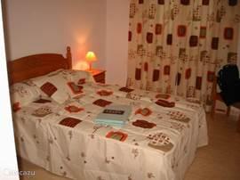 De hoofdslaapkamer met het tweepersoonsbed en grote garderobekast met schuifdeuren. Geen airco maar wel een ventilator.