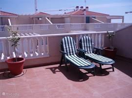 Zonnen op het dakterras met citroen- en sinaasappel boompjes. Een zonneluifel zorgt voor de nodige schaduw.