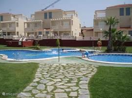 Het zwembad met kinderbad en jacuzzi heeft rondom een mooi gazon met douches en rieten parasols.