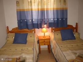 De 2-eenpersoonsbedden in de ruime slaapkamer met grote garderobekast. geen airco maar wel een ventilator. Als u de deur openlaat van de woonkamer koelt deze kamer ook af.