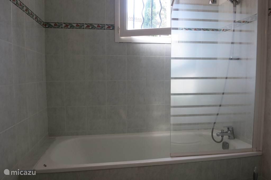 Badkamer,met bad, douche, wastafel en toilet. Deze is toegankelijk vanuit de hoofdslaapkamer