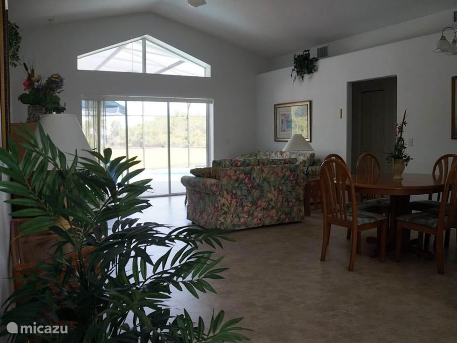 Een dele van de huiskamer met uitzicht op het terras, zwembad en het meer.