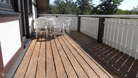 ons grote balkon met zicht op de eettafel met stoelen
