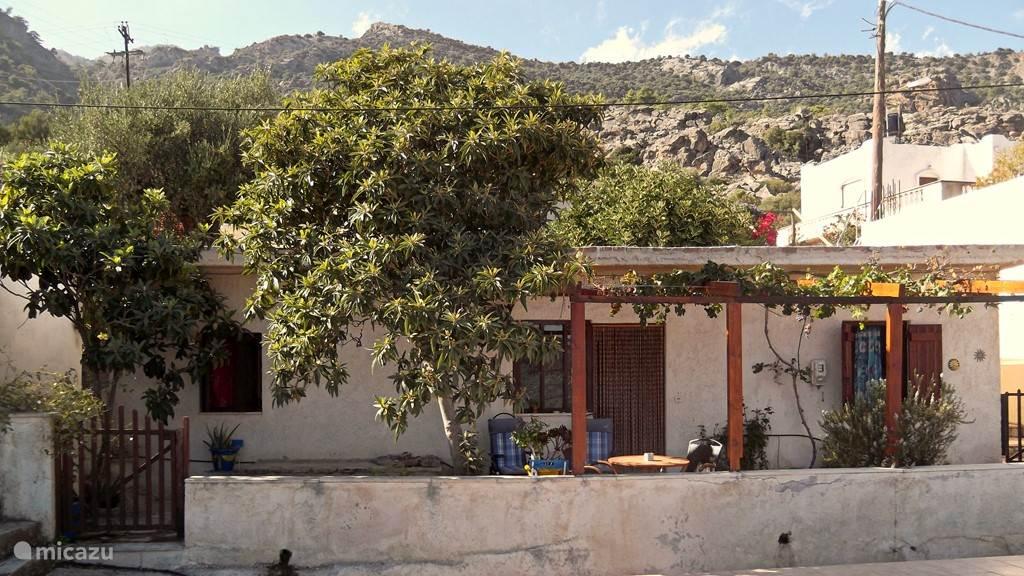 Vooraanzicht van Villa Helios. Het voorterras. In het midden de voordeur. Links en rechts daarvan de houten luiken van de slaapkamerramen.