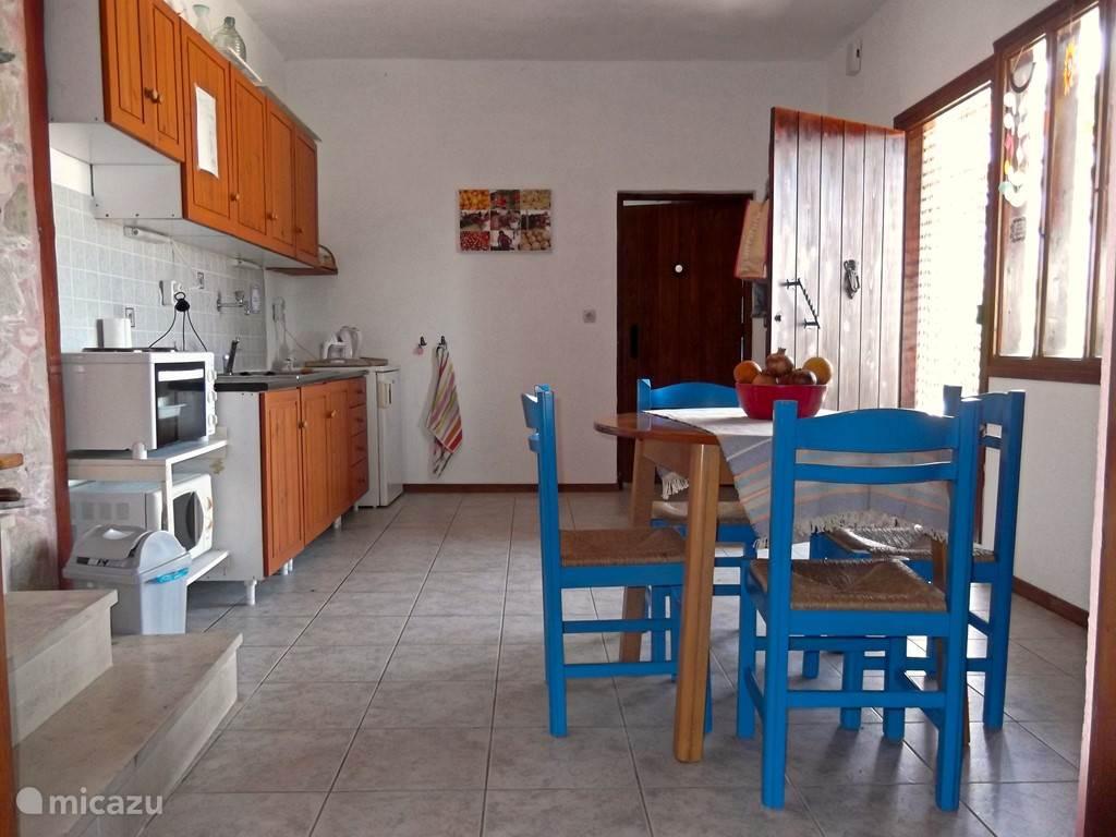De woonkeuken. Links het keukenblok, tegenover de voordeur. Geflankeerd door koelkast en elektrische kookplaten en oventje.