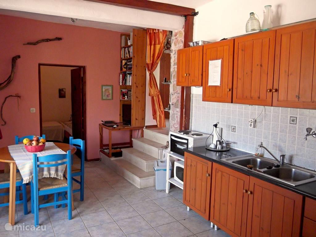 De woonkeuken. Met een doorkijk naar een van de twee slaapkamers en, het trapje op, naar het halletje met de deur naar toilet en douche.